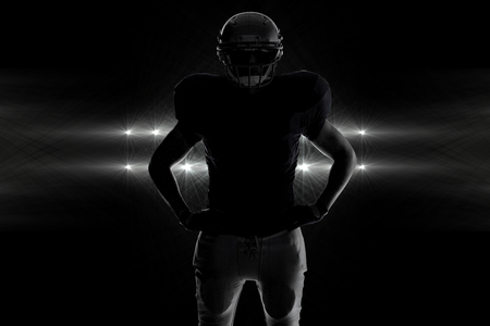 Silhouette American football player standing with hand on hip against spotlights