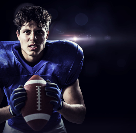 clenching teeth: Portrait of aggressive American football player against black Stock Photo