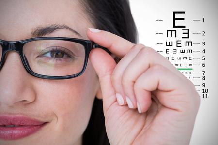 middleaged: Pretty brunette wearing eye glasses against eye test