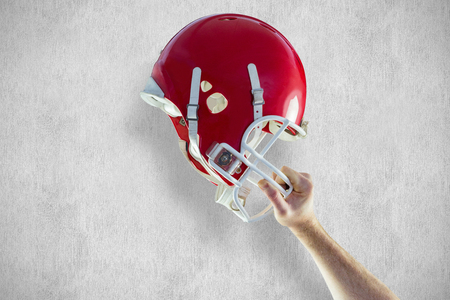 holding up: American football player holding up his helmet against white and grey background