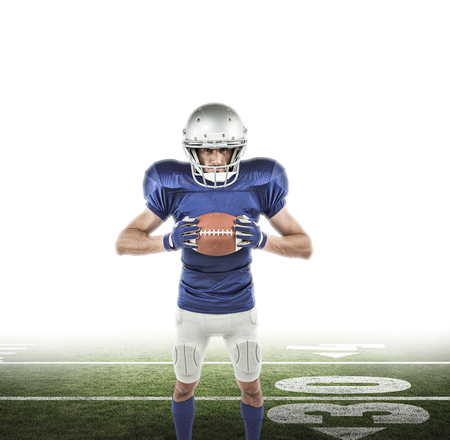 uniform green shoe: Full length portrait of American football player holding ball against american football pitch