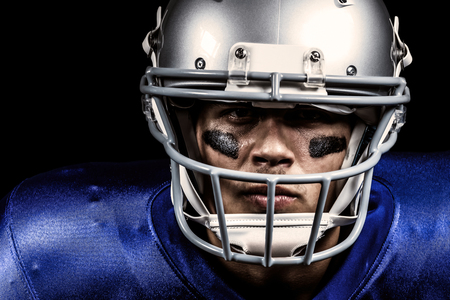 blue face: Determined American football player in uniform holding ball against black Stock Photo