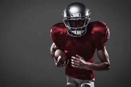 uniforme de futbol: jugador de fútbol americano corriendo con la pelota contra el gris Foto de archivo