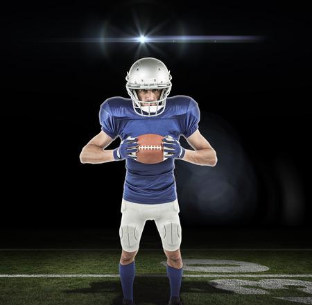 uniform green shoe: Full length portrait of American football player holding ball against lens flare Stock Photo