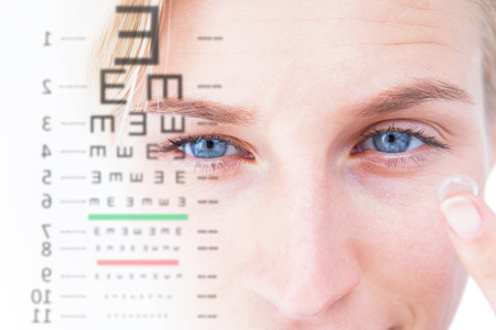 sense of sight: Pretty blonde applying contact lens against eye test