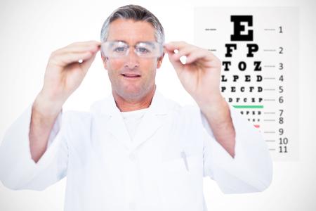 eye test: Optician in coat holding glasses  against eye test