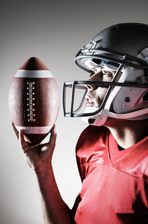 looking up: Sportsman looking up while holding American football against grey vignette Stock Photo