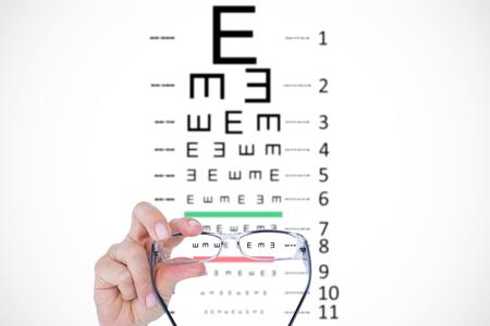 eye test: Hand holding glasses against eye test