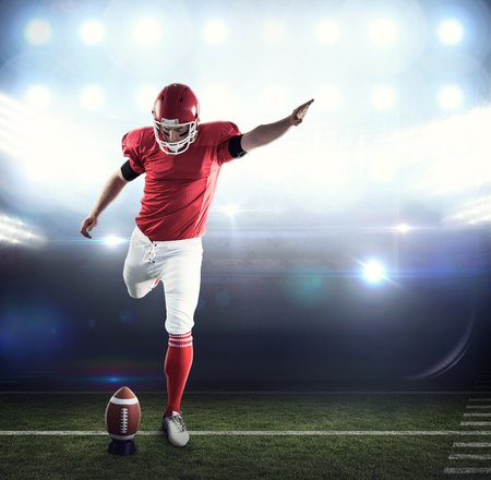 american football ball: American football player kicking football against american football arena Stock Photo
