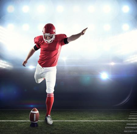 uniforme de futbol: jugador de fútbol americano patadas de fútbol americano contra el campo de fútbol Foto de archivo
