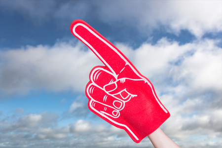 foam hand: American football player holding supporter foam hand against blue sky with clouds