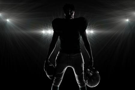 Silhouette American football player holding ball and helmet against spotlight
