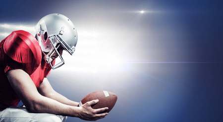 crouching: American football player crouching while holding ball against spotlights
