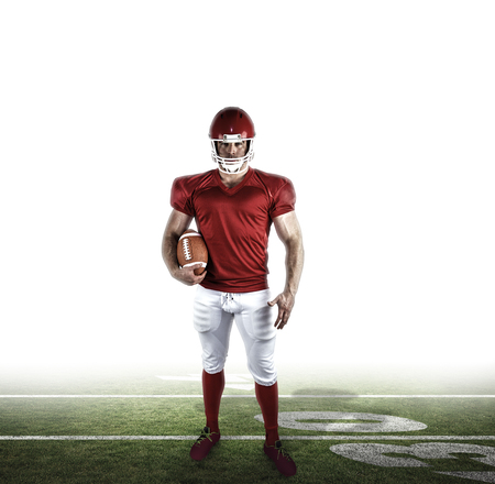 football pitch: American football player holding ball against american football pitch