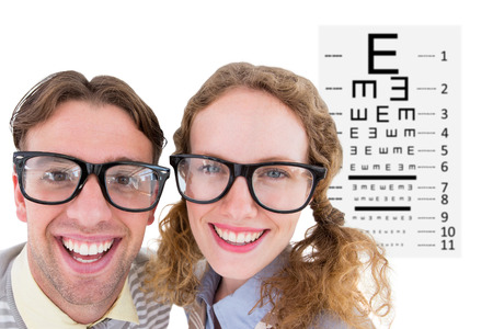 eye test: Happy geeky hipster smiling at camera  against eye test Stock Photo