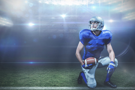 kneeling: American football player with ball kneeling against american football arena