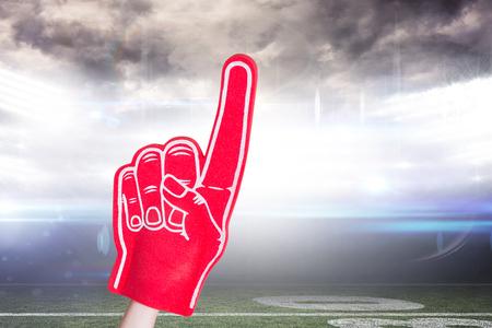 foam hand: American football player holding supporter foam hand against american football arena Stock Photo
