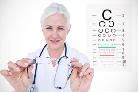 sense of sight: Smiling female optician presenting eye glasses against eye test Stock Photo