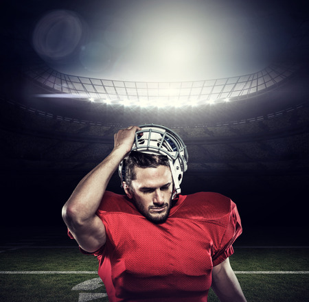 removing: American football player in removing helmet against american football arena