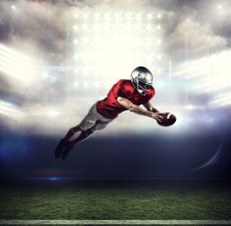 scoring: American football player scoring a touchdown against sports pitch Stock Photo