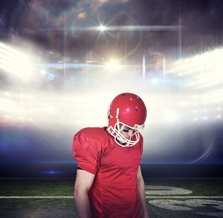unsmiling: Unsmiling american football player looking down against american football arena Stock Photo