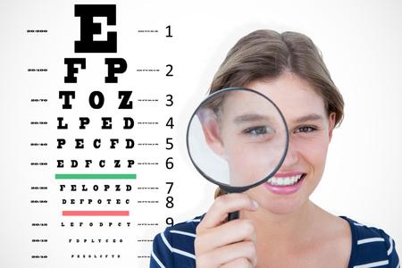 eye test: Smiling woman holding magnifying glass against eye test
