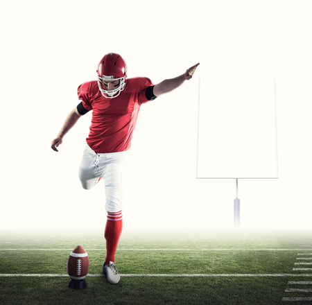 american football ball: American football player kicking football against american football posts Stock Photo