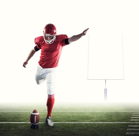 uniforme de futbol: jugador de fútbol americano patadas de fútbol contra los Mensajes de fútbol americano Foto de archivo