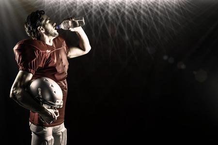 or thirsty: Jugador de f�tbol americano sed en el agua potable camiseta roja contra focos