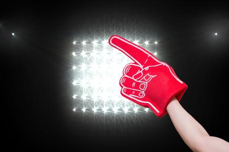 foam hand: American football player holding supporter foam hand against spotlight Stock Photo