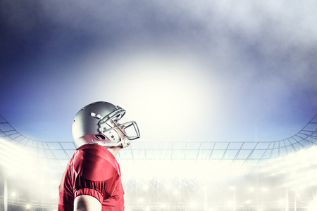 looking up: American football player looking up while standing against rugby stadium Stock Photo