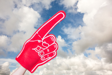 foam hand: American football player holding supporter foam hand against blue sky with white clouds