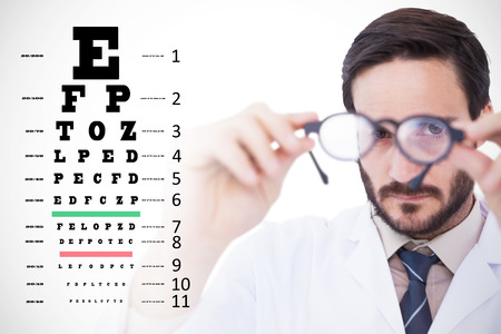 eye test: Doctor wearing lab coat looking through eyeglasses against eye test Stock Photo