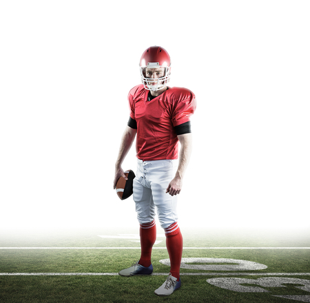 football pitch: Portrait of american football player holding football against american football pitch Stock Photo