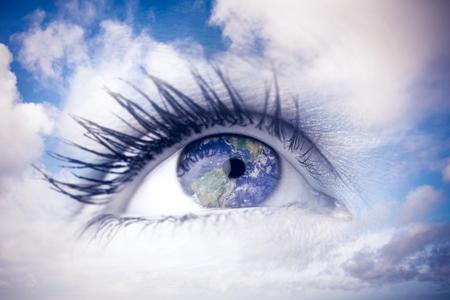 mujer mirando el horizonte: Ojo azul contra el cielo azul con nubes blancas Foto de archivo