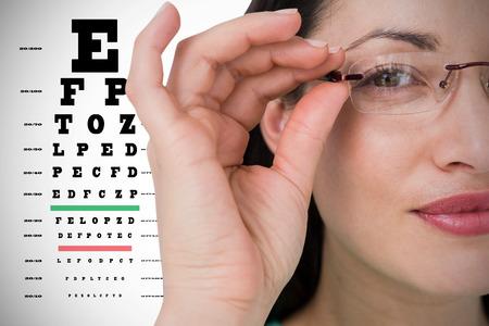 eye test: Pretty brunette wearing eye glasses against eye test