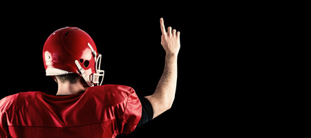 triumphing: Rear view of american football player triumphing  against black Stock Photo