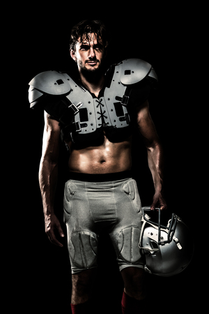 padding: Shirtless American football player with padding holding helmet against black