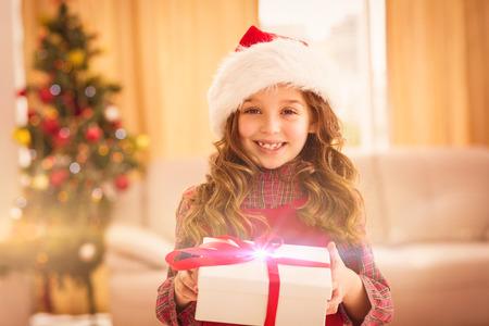 ni�as sonriendo: Festiva apertura de la ni�a un regalo en el pa�s en la sala de estar Foto de archivo