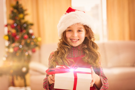 santa hat: Festive little girl opening a gift at home in the living room Stock Photo