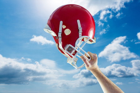 holding up: American football player holding up his helmet against blue sky