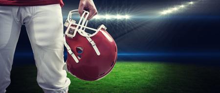 casco rojo: Un jugador de f�tbol americano de tomar su casco en la mano contra el estadio de rugby