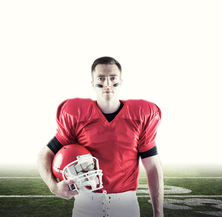 football pitch: American football player holding helmet against american football pitch