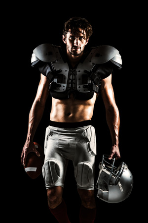 padding: Shirtless American football player with padding holding ball and helmet against black
