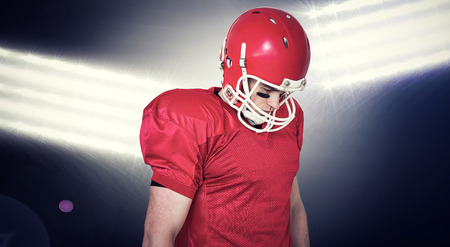 unsmiling: Unsmiling american football player looking down against spotlights