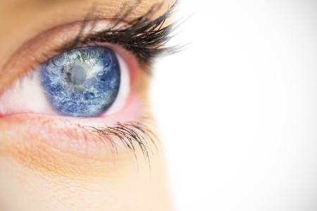 blue eye: Close up of female blue eye against earth