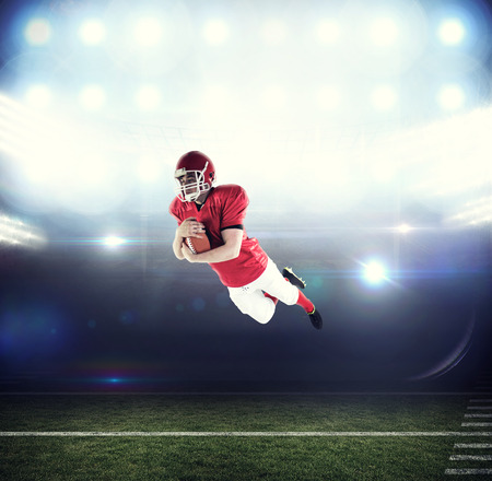 scoring: American football player scoring a touchdown against american football arena