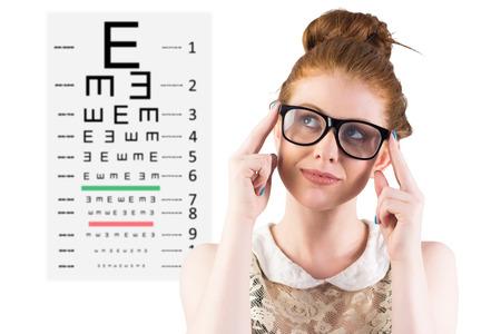 vision test: Hipster pelirroja mirando hacia arriba pensando contra examen de la vista Foto de archivo