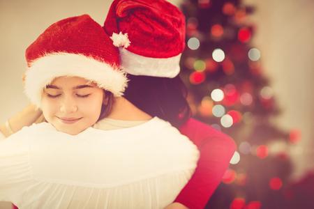 personas abrazadas: Madre e hija abrazos en la Navidad en casa en el sal�n Foto de archivo