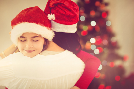 women hugging: Mother and daughter hugging at christmas at home in the living room